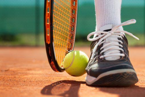 Legs of sportive man  near the tennis racquet and balls